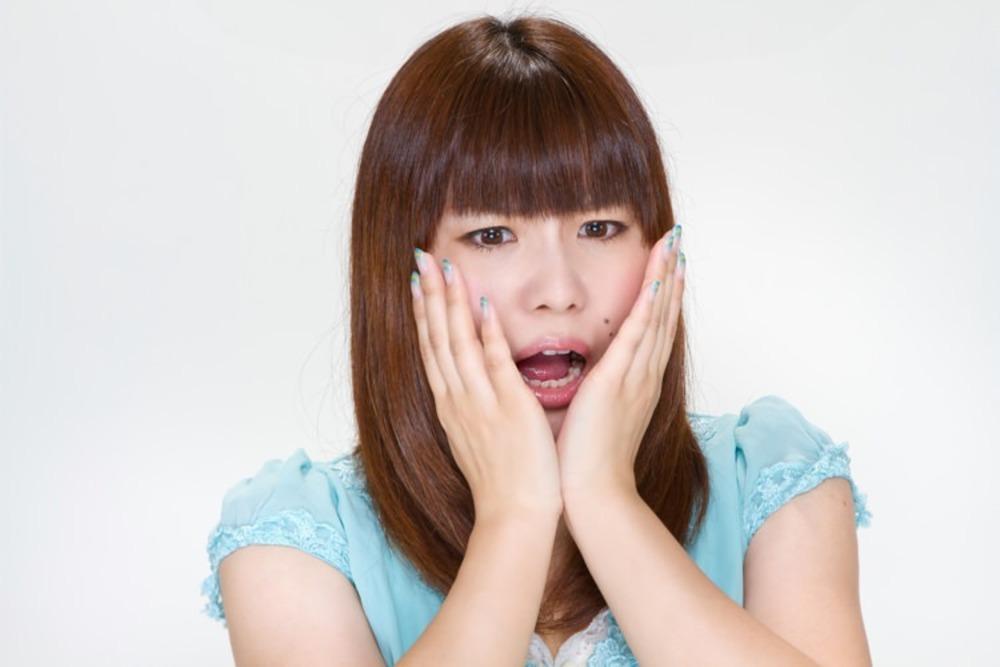 ショックを受けている表情の女性写真。