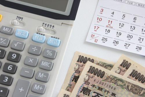 電卓機と現金の写真。