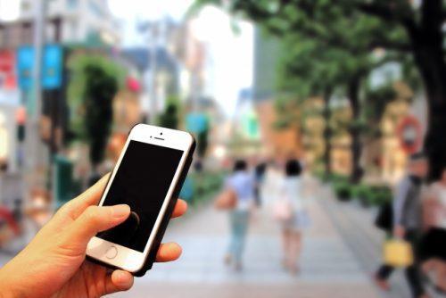 街中でスマートフォンを操作する手の写真。