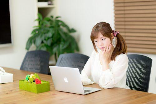 パソコン画面を見つめる女性の写真