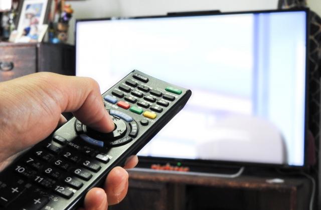 テレビをリモコンで操作している様子。